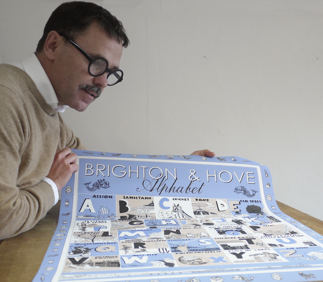 Alej ez with his 'Brighton and Hove Illustrated Alphabet' that shows in alphabetical order places, events and people that we love in Brighton and Hove.